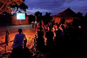 Den!ui, Namibia. Die erste Kinovorführung, die es jemals in dem Dorf in der Kalahari gegeben hat im Jahr 2015 (© Tracking in Caves).